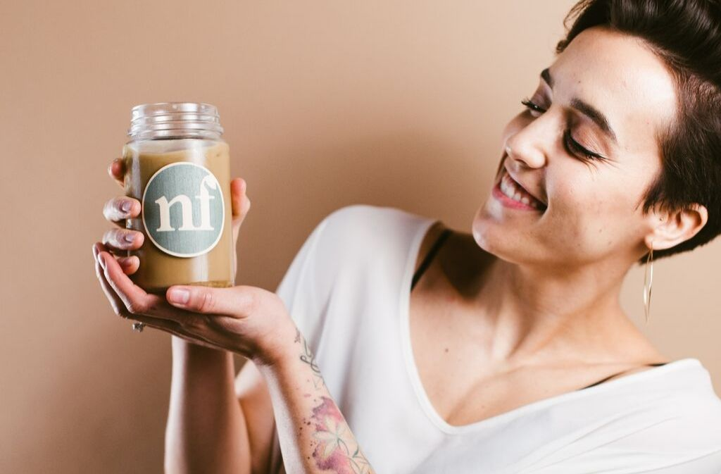 woman smiling and holding up a glass of low carb salted caramel cold brew