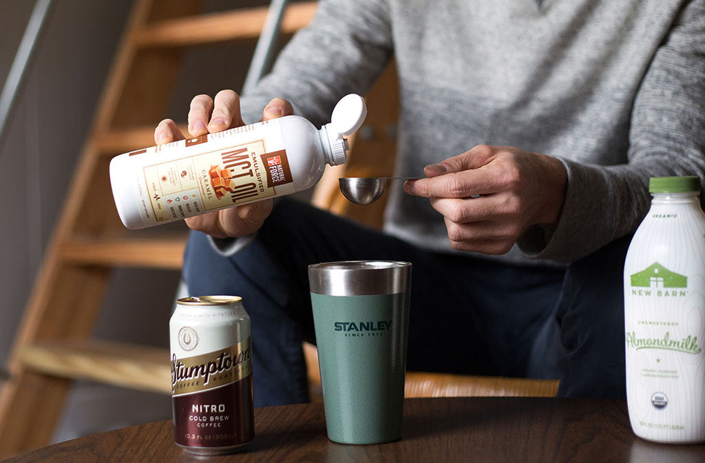 man pouring a tablespoon of natural force keto coffee creamer for a keto iced coffee
