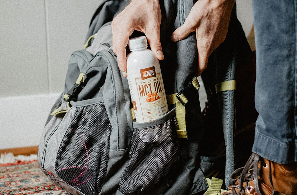 hand putting natural force keto coffee creamer into the side of a backpack