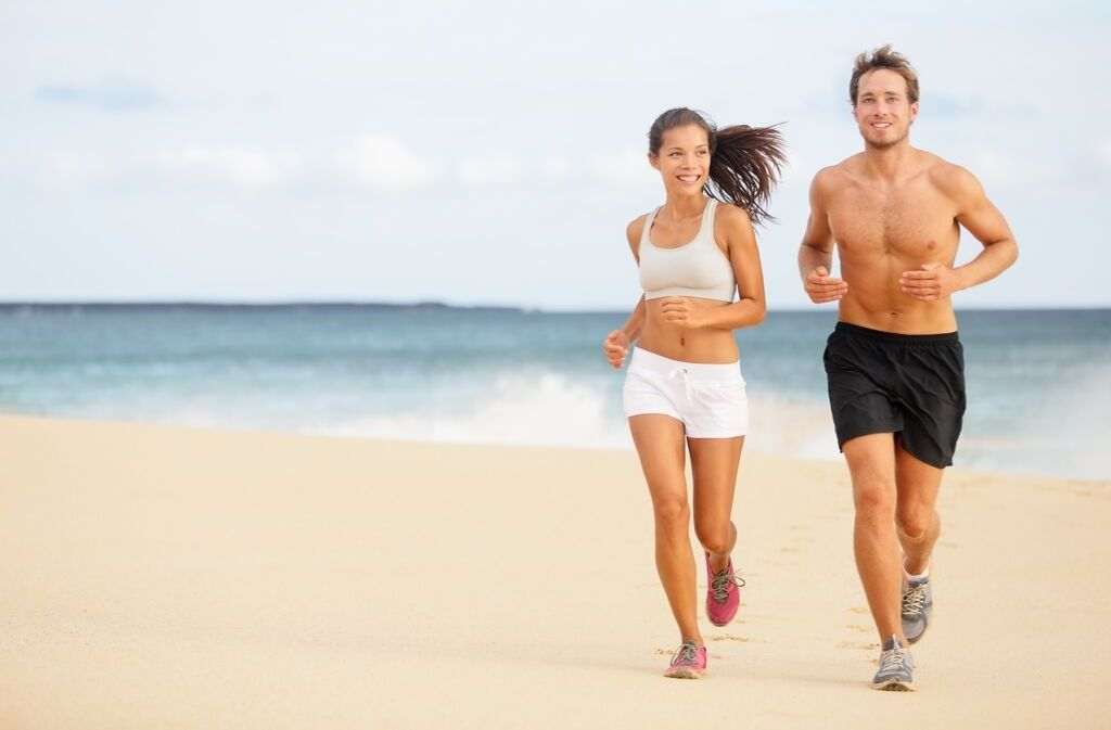 man and woman staying in shape while traveling by jogging on the beach