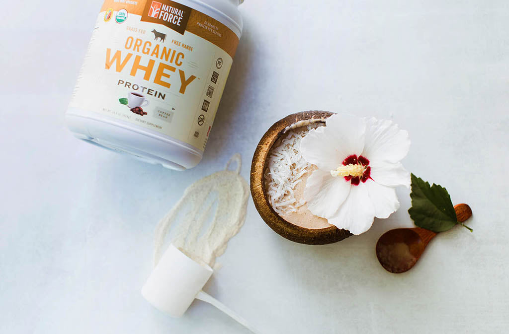 bowl of mushroom smoothie beside natural force organic coffee whey protein