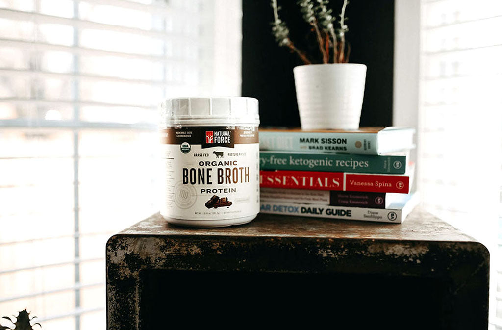Container of natural force organic bone broth protein beside a stack of books