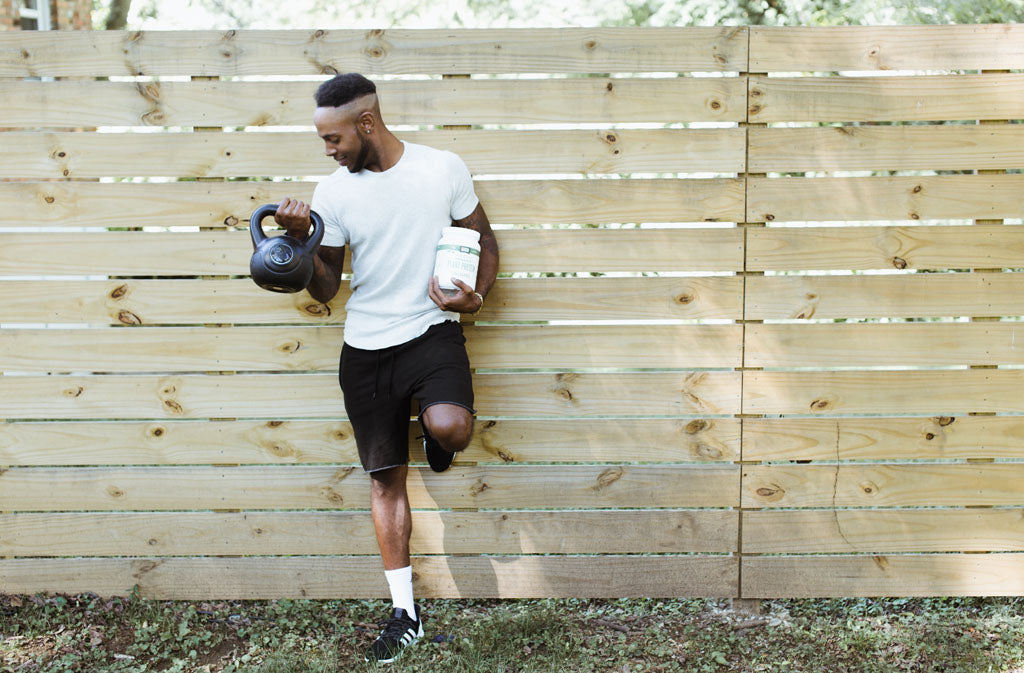 man leaning against a wood fence doing a bicep curl and holding a container of natural force organic plant protein