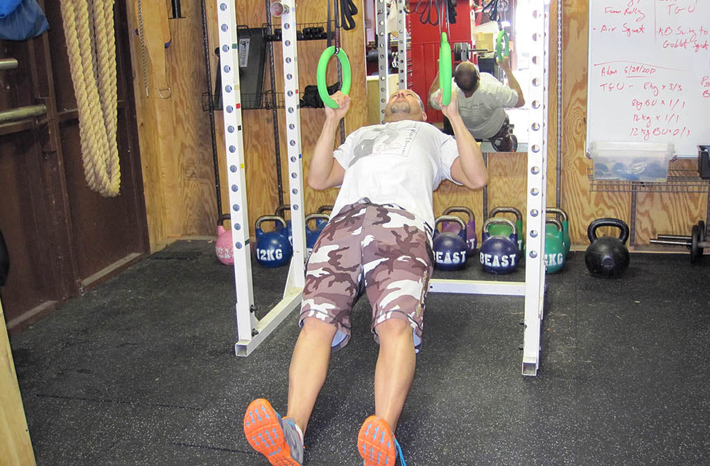 man in finishing position for ring rows