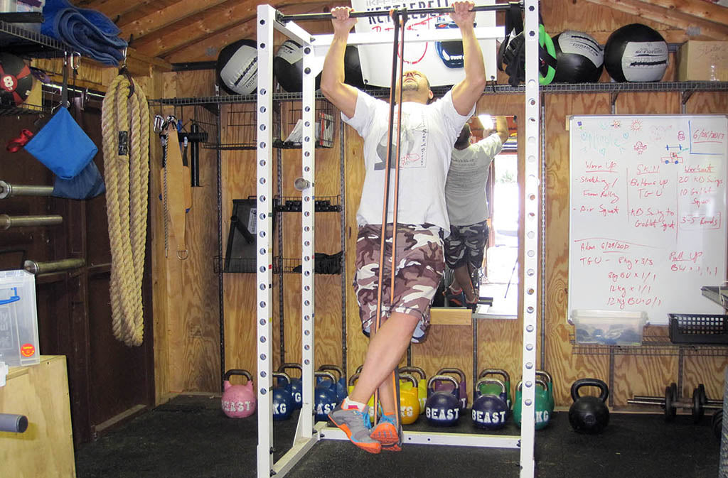 man doing banded pull up
