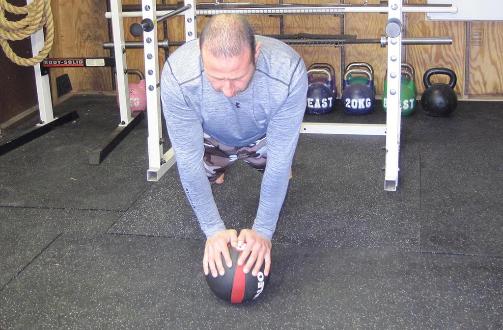 man at top of med ball push up