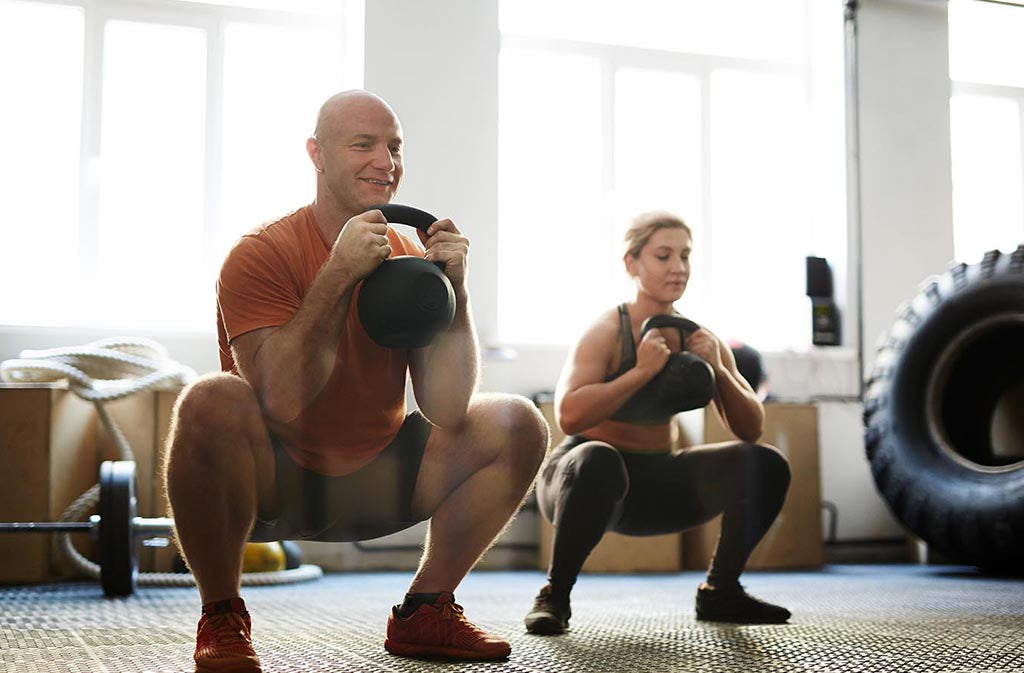 man and woman squatting while holding kettlebells