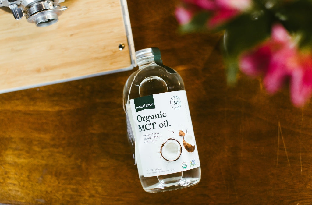natural force organic mct oil bottle on a wood surface