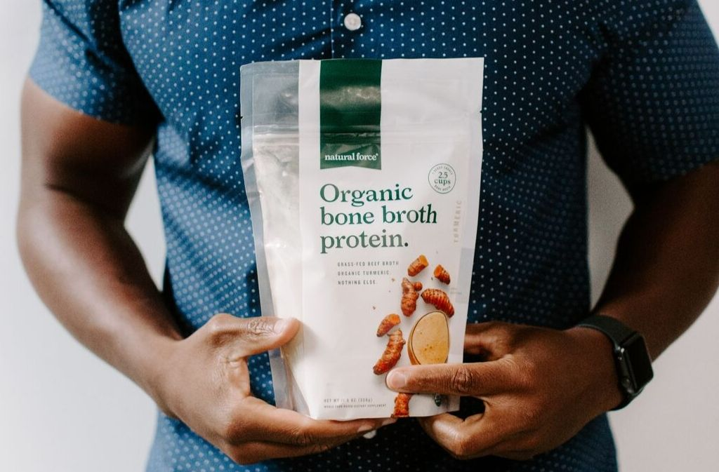 fit man in a blue shirt holding a bag of natural force organic bone broth protein