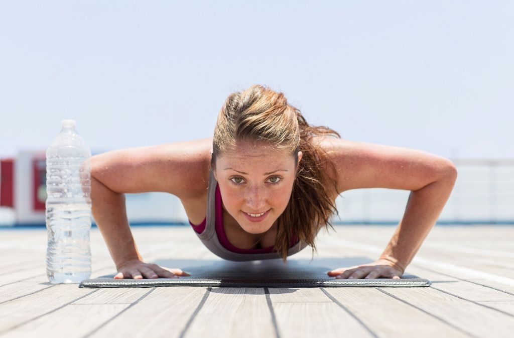 a woman at the bottom of a push up looking at the camera and smiling