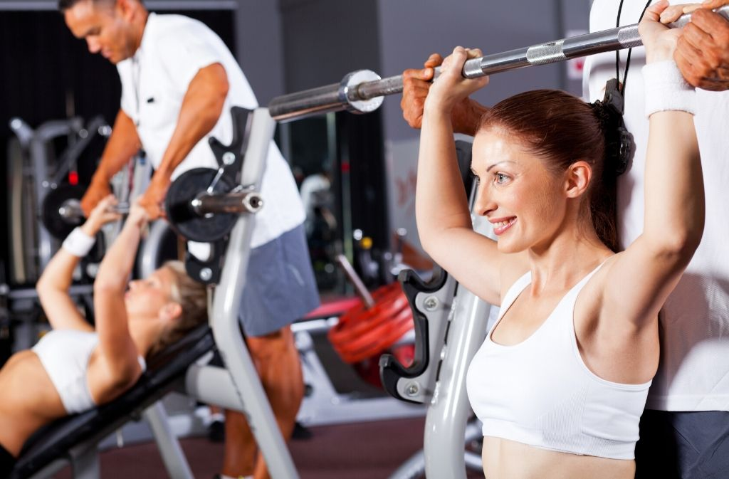 athletic woman in a white sports bra smiling while doing a seated shoulder press while a man stands behind her lightly supporting the weight of the bar