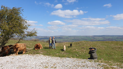 Photo shoot in field with family wearing sheepskin coats with dogs running and photographer taking photos
