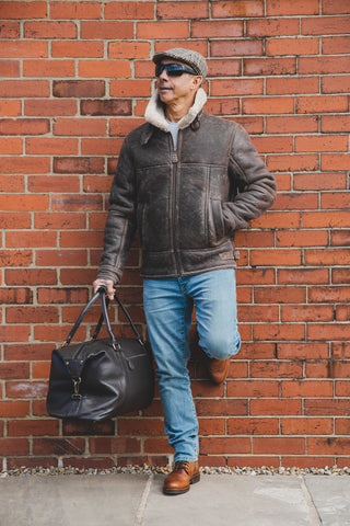 Man lent against brick wall with foot up holding 201-100 nordvek brown leather holdall
