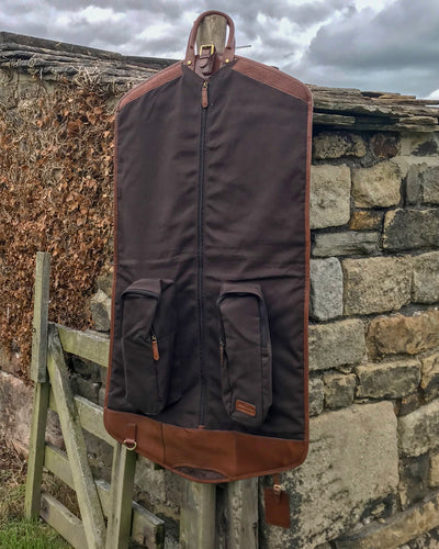 Ashwood chestnut leather Suit Carrier hung up open against stone wall