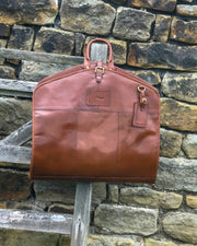 Ashwood leather Suit Carrier closed hung up on gate against stone wall chestnut