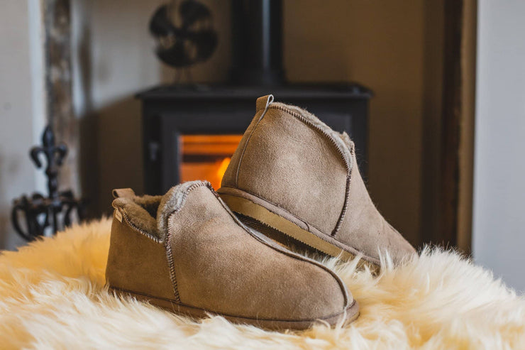 Shepherd Mens sheepskin slippers ANTON Stone pair in front of fire