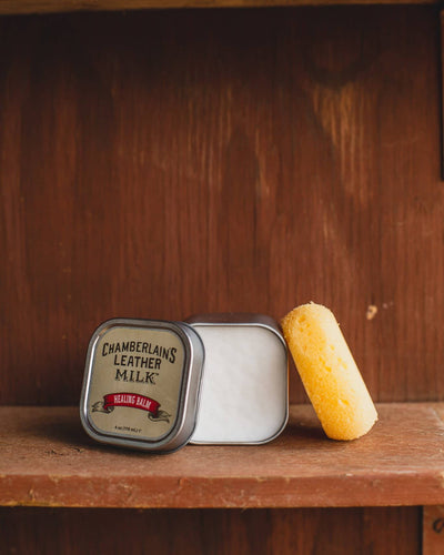 Chamberlins Leather Milk Healing balm on wooden shelf open with sponge
