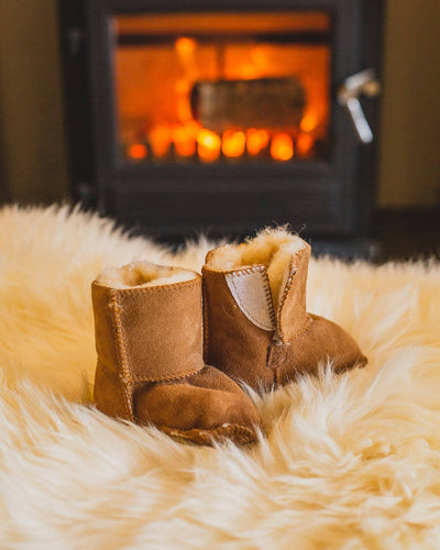 Nordvek baby booties 408-100 chestnut on rug infront of fire