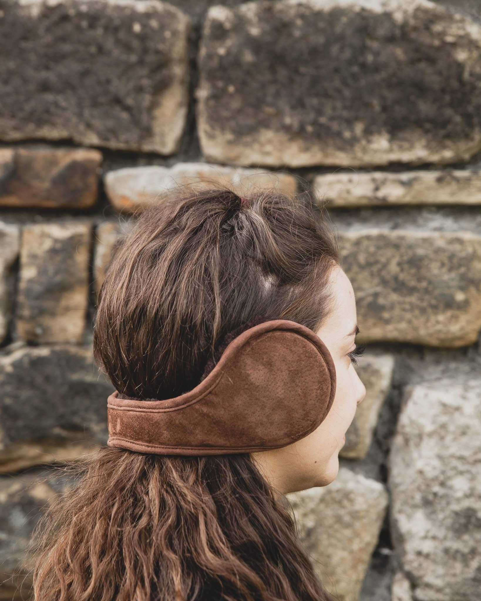 Nordvek adults sheepskin earmuffs 513-100 chocolate model wearing in front of stone wall
