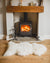 Nordvek sheepskin single rug 601-100 natural in front of fire