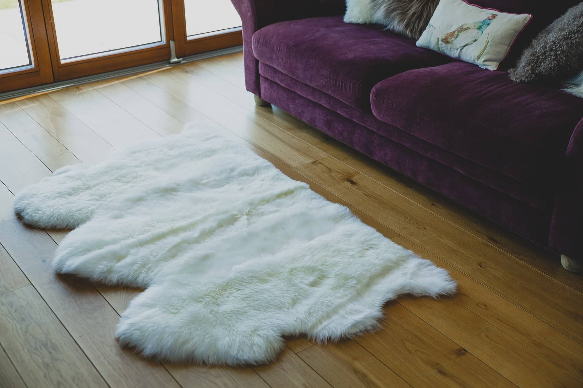 Nordvek sheepskin  natural rug 603-100 triple in front of sofa close up