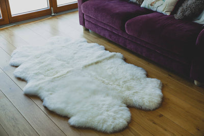 Nordvek sheepskin  natural rug 604-100 quad in front of sofa close up