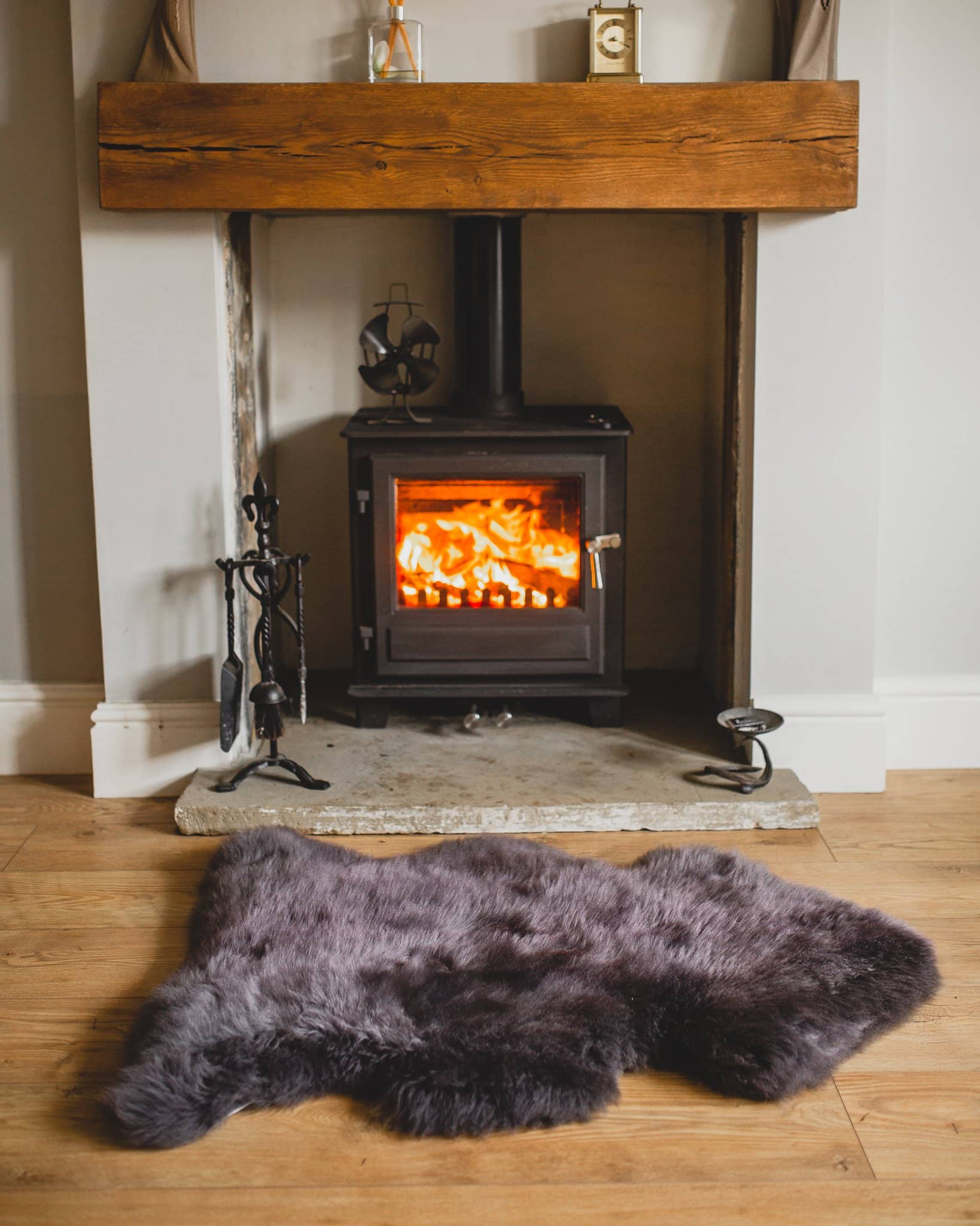 Nordvek sheepskin rug coloured grey in front of fire