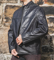 Nordvek mens leather jacket 712-100 black on model zipping up stone wall