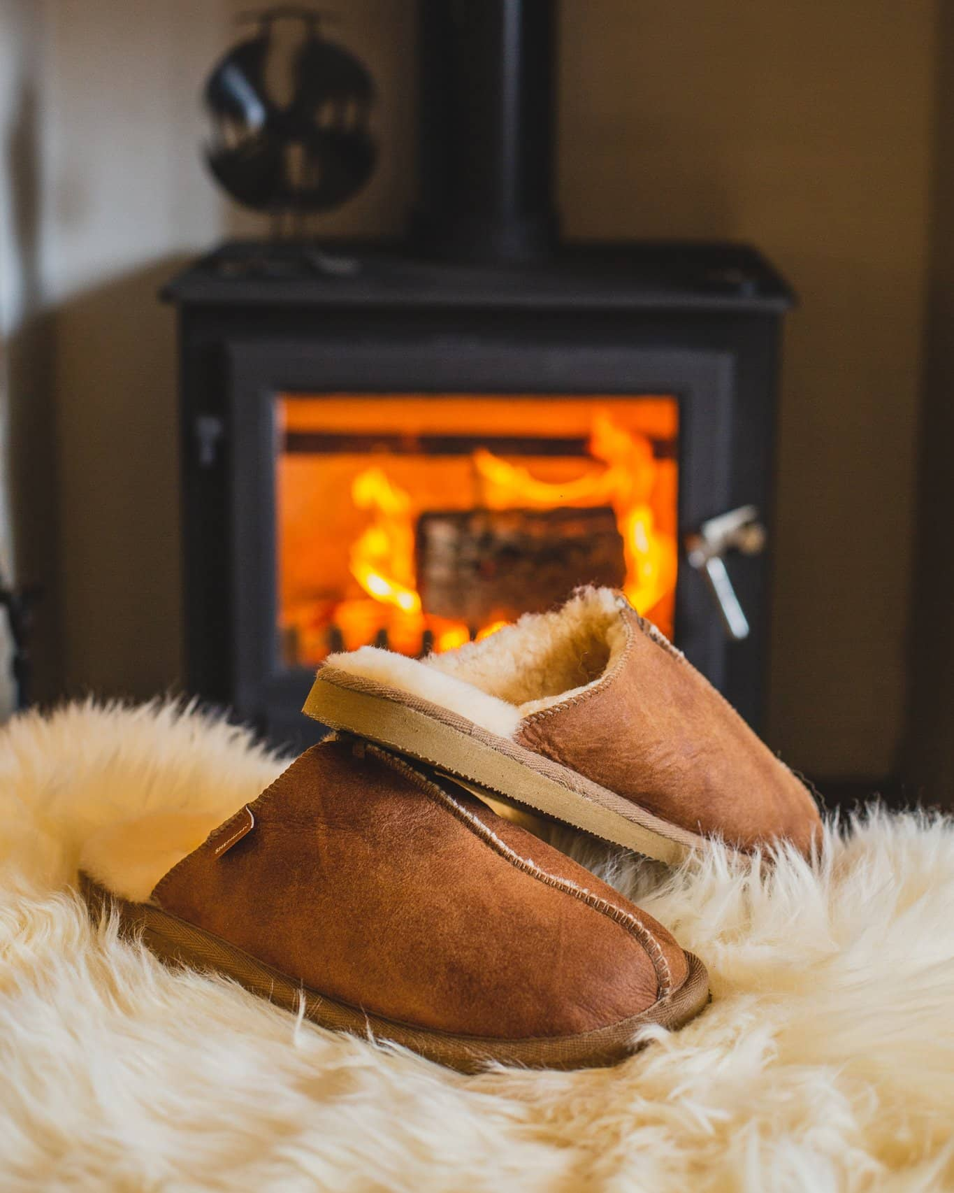 Shepherd Mens sheepskin slippers HUGO cognac pair in front of fire