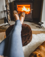 shepherd womens sheepskin slippers SAGA leopard model wearing slippers in front of fire