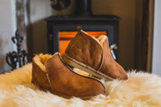 Shepherd womens sheepskin slippers ANNIE cognac model slippers in front of fire