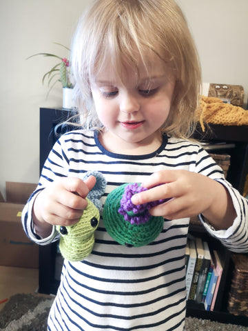 Play based learning with SBKM Spring Play Set. Ava holding a crocheted butterfly and lavender plant