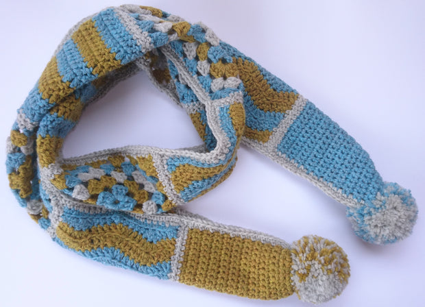 Beginner crochet squares - shown is a blue, mustard, and grey scarf made from crochet squares - pictured against a white background