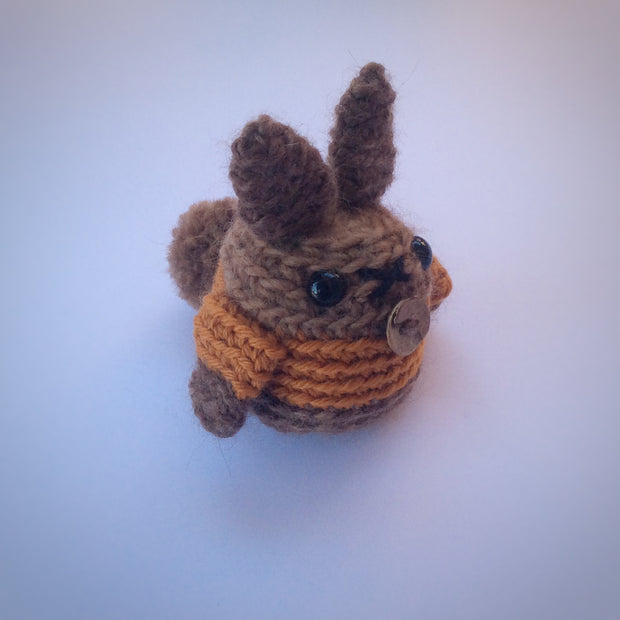 Brown amigurumi bunny made in the round. Wearing an orange jacket and pictured on a white background