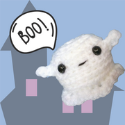 "Halloween amigurumi ghost pattern. Picture shows a crocheted ghost saying ""Boo!"" in front of a haunted house"