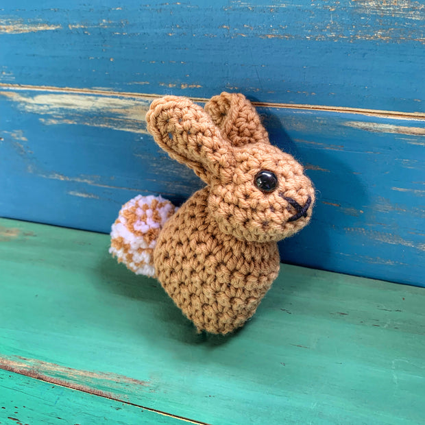 Brown crocheted bunny with brown and white tail on blue and green wooden background