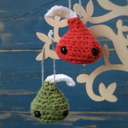 free amigurumi pattern pdf - green and red Chocolate kisses hung on a tree in front of a blue wooden background