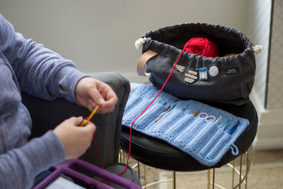 Learn to crochet near me. Image shown is woman working on crochet project with crochet case and project bag.