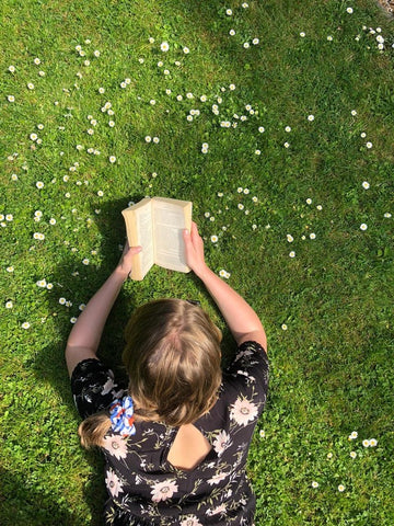 Woman laying in green grass reading a book with a daisy print hair scrunchie in hair