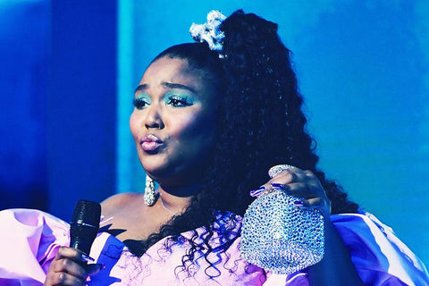 Lizzo performing on stage in an 80's style purple dress with a jewelled silver scrunchie and a blue background