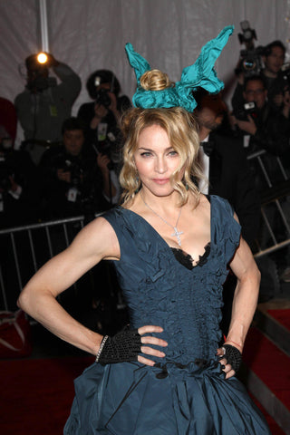 Madonna on red carpet with elaborate blue silk scrunchie and navy blue gown