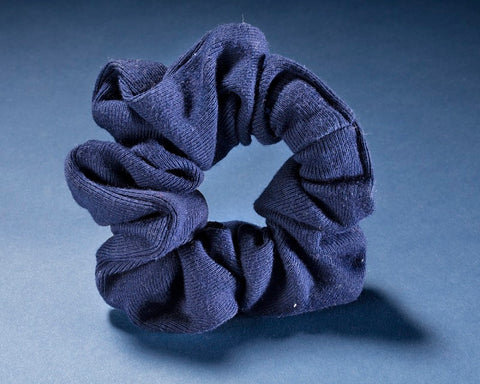 blue fabric hair scrunchie with a light blue background