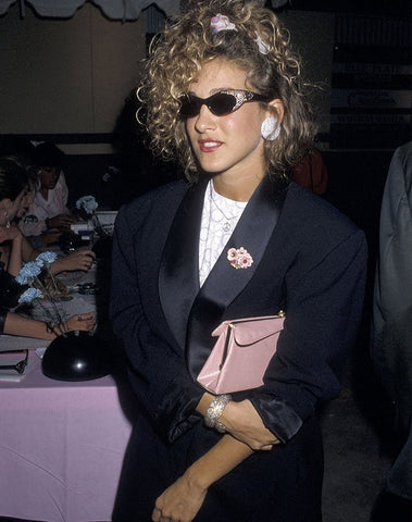 Sarah Jessica Parker in 90's scrunchie with black jewelled sunglasses and black satin blazer holding a light pink purse