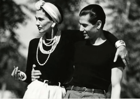 black and white image of man in black t shirt and woman in white twist knot headband and pearls