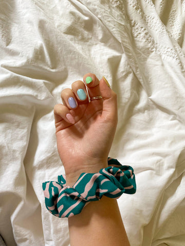 hand with painted pastel nails and a green and pink animal print zebra hair scrunchie around wrist