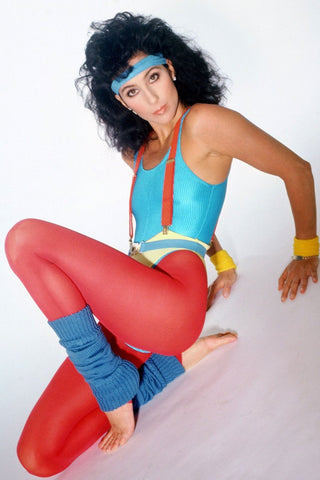 cher in 80s workout gear with bright red leggings blue leg warmers and red suspenders