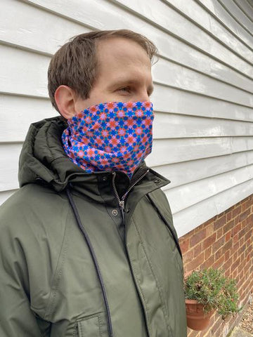 image of man in snood neck warmer designed with pink and blue geometric shapes
