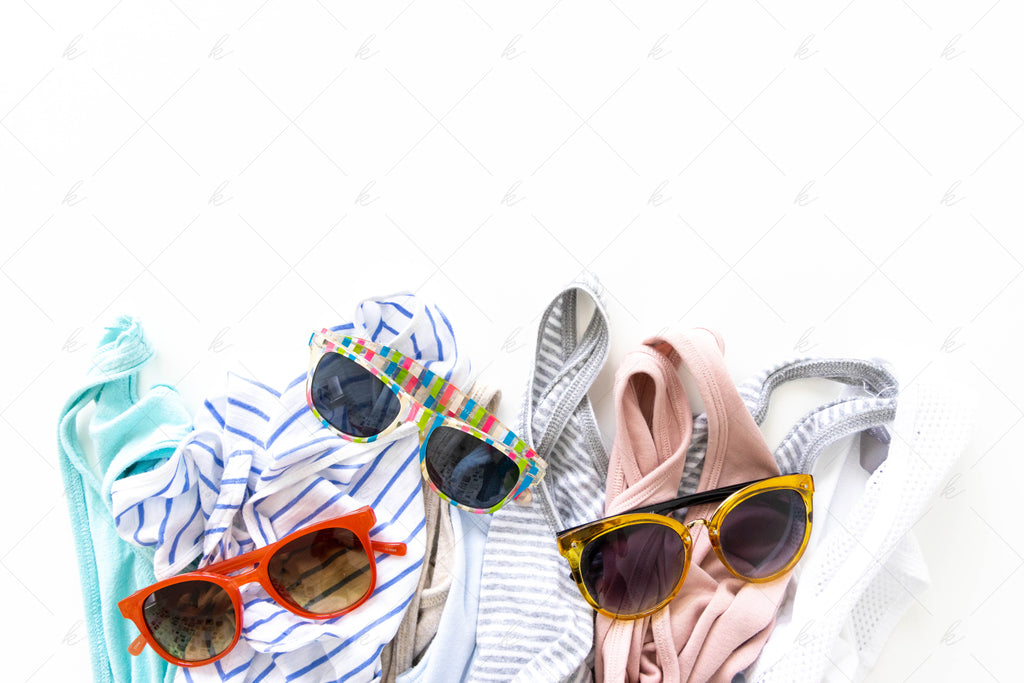 various tank tops, teal, blue, pink, grey, and white with sunglasses summer stock photo