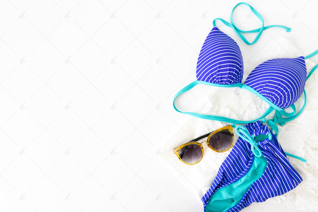 blue and teal striped bathing suit with yellow sunglasses summer stock photo
