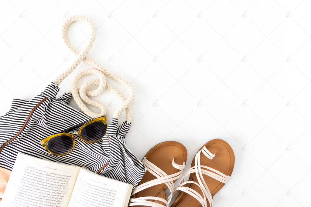 book, yellow sunglasses, blush striped bag and neutral sandals summer stock photo
